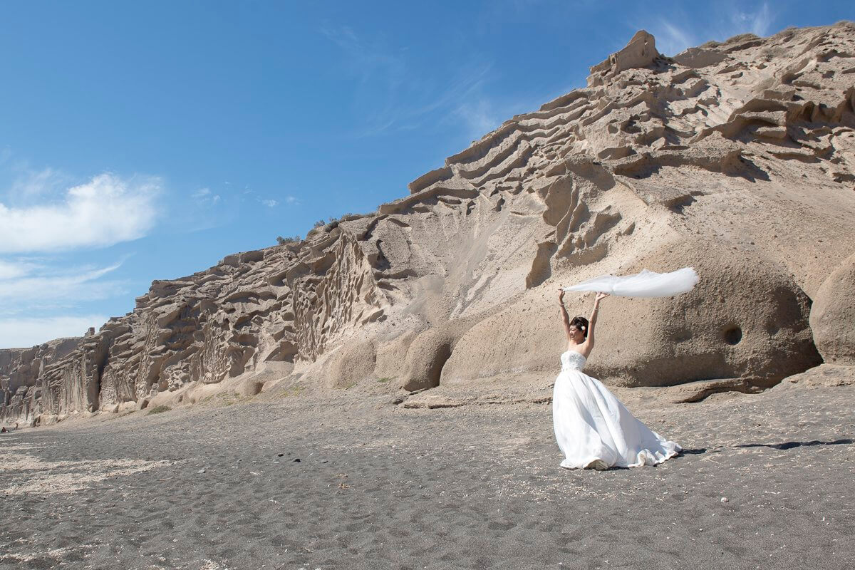 bride posing at white beach at Santorini