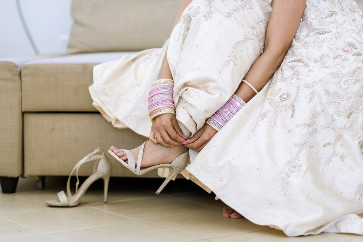 indian bride wearing her wedding shoes